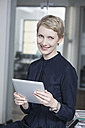 Germany, Munich, Businesswoman in office, using digital tablet - RBYF000532