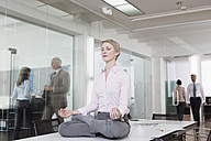 Germany, Munich, Businesswoman in office, meditating on desk - RBYF000580