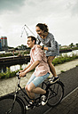 Young couple driving together on bicycle - UUF001017