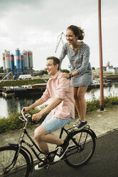Young couple driving together on bicycle - UUF001044