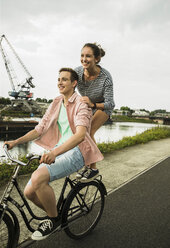 Young couple driving together on bicycle - UUF001045