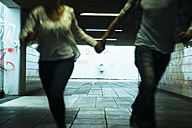 Young couple running hand in hand in a dark underpass, partial view - UUF001073
