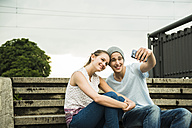 Young couple taking a selfie with smartphone on stairs - UUF001088
