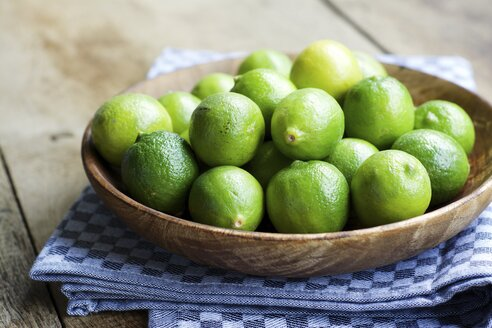 Key limes, Citrus aurantiifolia, in a wooden bowl - HAWF000313