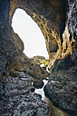 New Zealand, Golden Bay, Wharariki Beach, sea cave in the rocks with a little stream at low tide - SHF001448