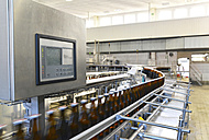 Germany, beer bottles on an assembly line of a bottling plant of a brewery - SCH000289