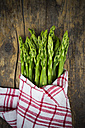 Bunch of green asparagus, Asparagus officinalis, wrapped in kitchen towel lying on dark wood - LV001448