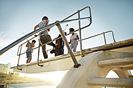 Friends playing urban golf on highboard of a swimming pool - VV000123
