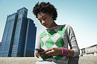 Young woman looking at cell phone outdoors - VVF000134