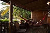 Caribbean, Trinidad and Tobago, Tobago, Castara, woman in hamock on porch - SKF001553