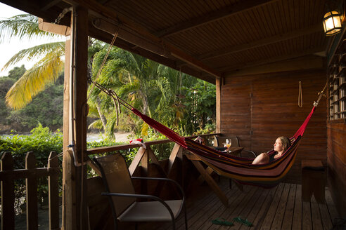 Caribbean, Trinidad and Tobago, Tobago, Castara, woman in hamock on porch - SKF001553
