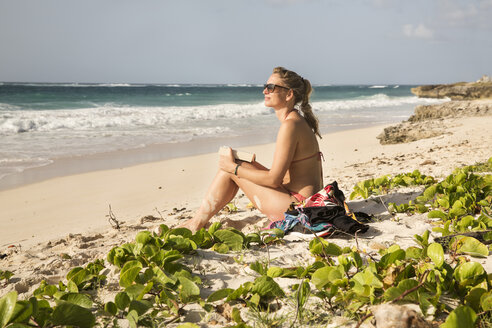 Caribbean, Barbados, woman sitting by the beach - SKF001559