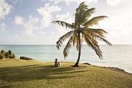 Caribbean, Barbados, woman sitting at the coast - SKF001568
