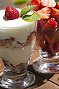 Strawberries in a glass and strawberries with yogurt and muesli in a glass, garnished with lemon balm - YFF000184