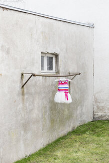 Germany, glum backyard with children's dress hanging on clothes pole - DR000694