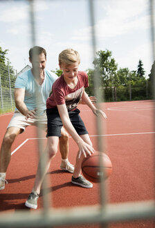 Germany, Mannheim, Father and son playing basket ball - UUF001176