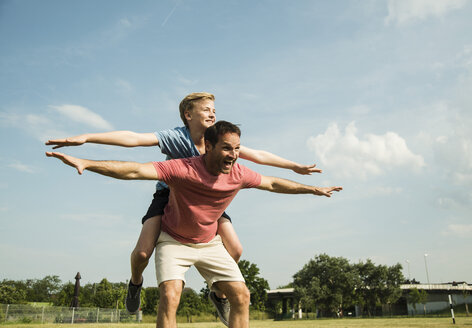 Germany, Mannheim, Father and son pretending to fly - UUF001132