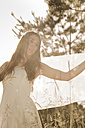 Portrait of teenage girl wearing white dress standing on meadow at backlight - FCF000267