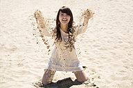 Portrait of smiling young woman throwing with sand - GDF000334