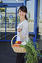 Portrait of smiling young woman carrying basket with fresh vegetables - GDF000340