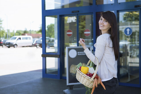Portrait of smiling young woman carrying basket with fresh vegetables - GDF000341