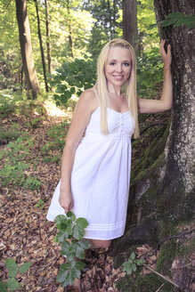 Portrait of a young woman leaning on tree trunk in the forest - VTF000310