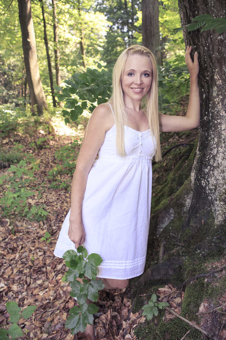 Portrait of a young woman leaning on tree trunk in the forest - VTF000310 - Val Thoermer/Westend61