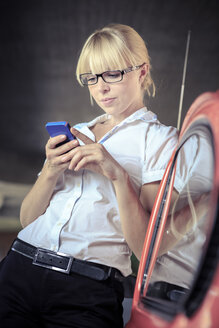 Portrait of young woman with smartphone leaning on car - VT000317