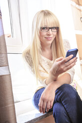Portrait of a young woman using smartphone at home - VTF000324