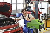Car mechanic adjusting headlight - SCH000304