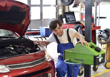Car mechanic adjusting headlight - SCH000305