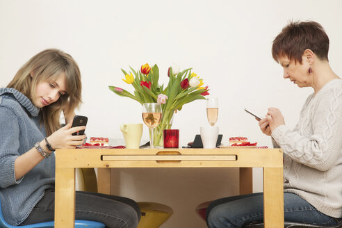 Germany, Berlin, Mother and daughter, using smart phone - MMFF000011