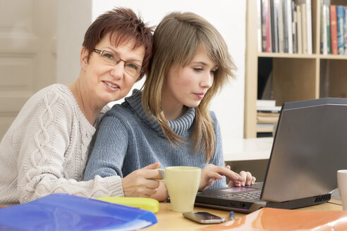Germany, Berlin, Mother and daughter using laptop - MMFF000029