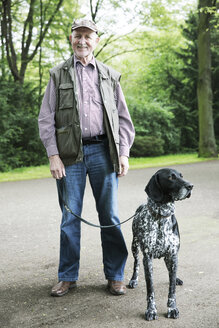Senior man walking with his German Shorthaired Pointer in city park - JATF000733