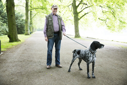 Senior man walking with his German Shorthaired Pointer in city park - JATF000735