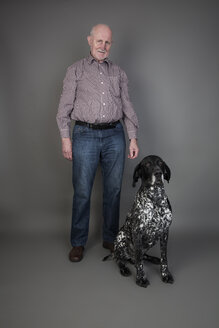 Senior man with his German Shorthaired Pointer in front of grey background - JATF000737