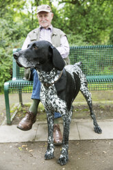 Senior man sitting on park bench with his German Shorthaired Pointer in the foreground - JATF000755