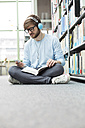 Student in a university library sitting on floor with headphones - WESTF019577