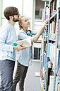 Two students in a university library taking book from shelf - WESTF019603