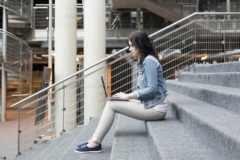 Young woman using laptop on stairs - WESTF019622