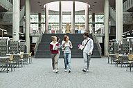 Group of students walking in a university library - WESTF019683