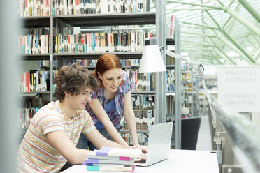 Two students in a university library using laptop - WESTF019716