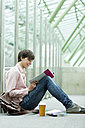 Student in a university library sitting on floor reading book - WESTF019737