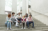 Group of students with books sitting on stairs - WESTF019758