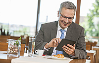 Businessman in restaurant with digital tablet - DISF000844