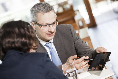 Businessman and businesswoman talking in restaurant - DISF000855