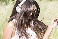 Portrait of young woman with headphones sitting in corfield - DRF000702