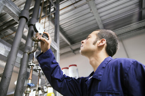 Technician working in a technical room looking at gauge - SGF000793