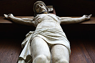Germany, Bavaria, Dornach, sculpture of crucified Jesus Christ, view from below - AXF000702