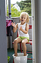 Portrait of little girl taking foot bath on balcony - JFEF000436